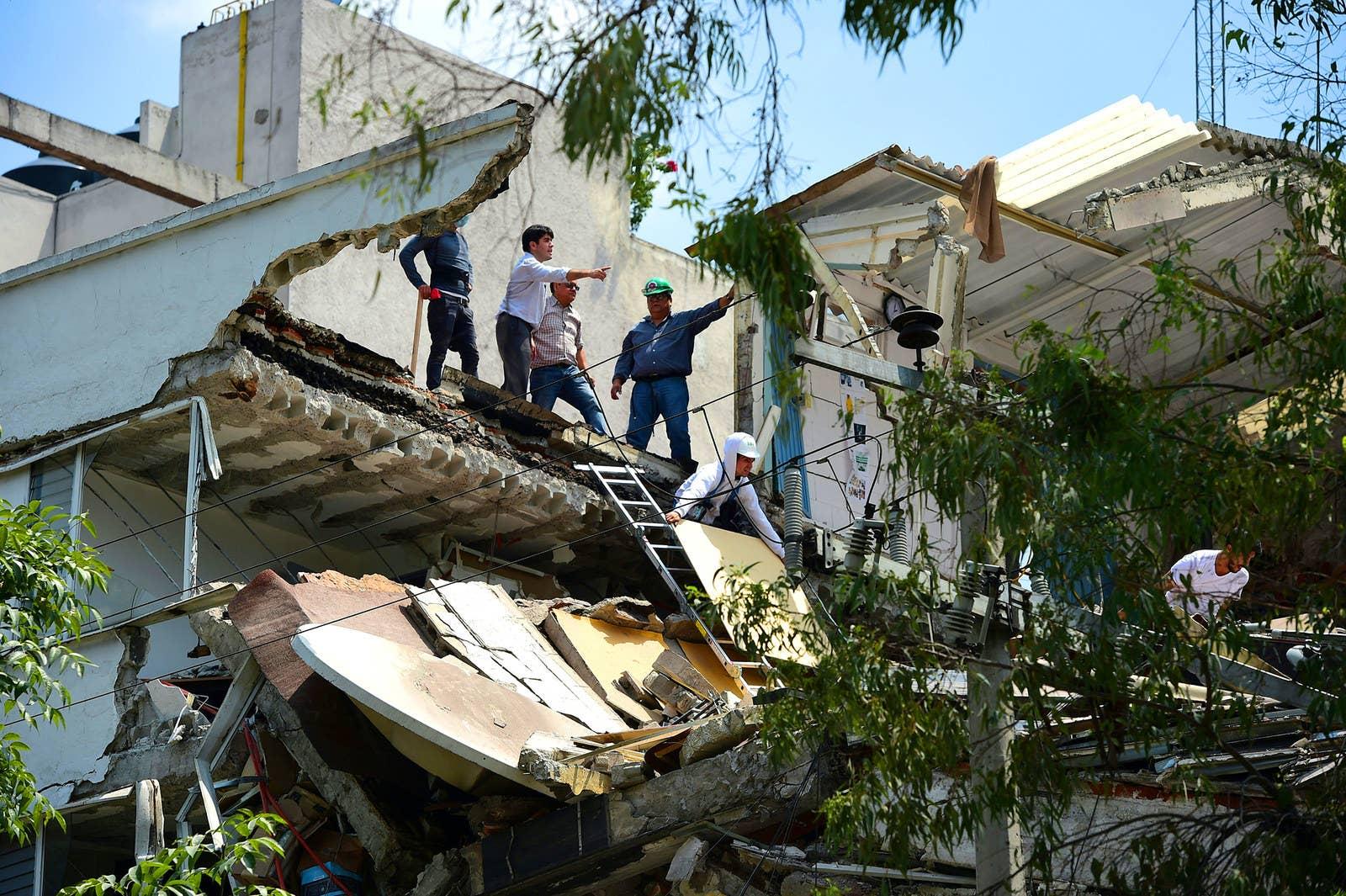 Personas buscan sobrevivientes en un edificio que colapsó en la Ciudad de México.
