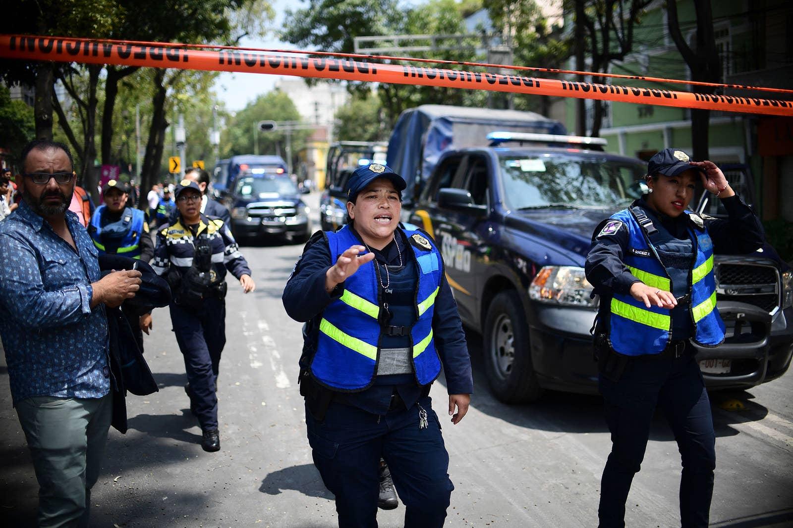 Oficiales de policía acordonan el área luego de que un edificio colapsara.