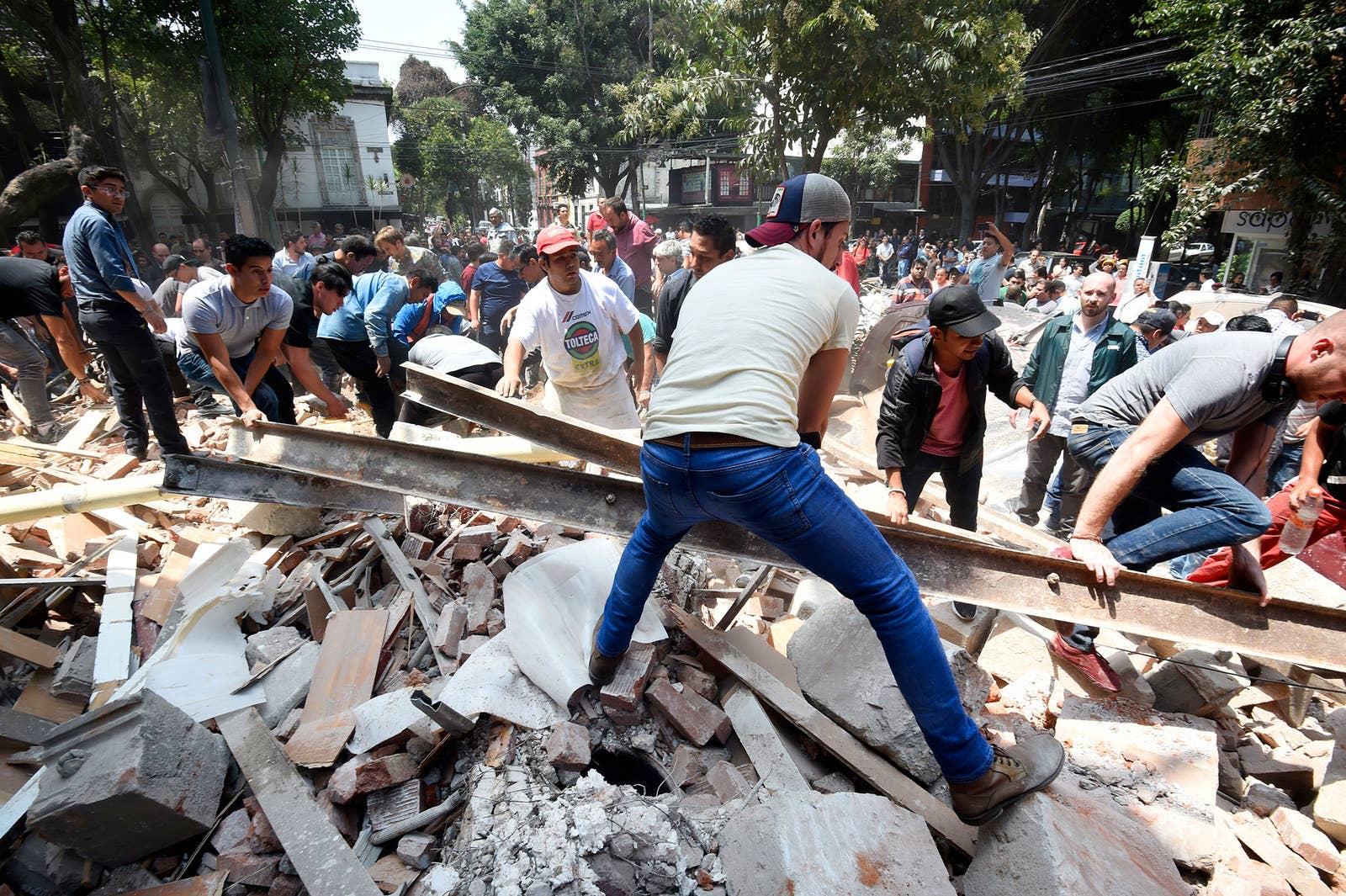 Personas remueven los escombros de un edificio que se derrumbó en la Ciudad de México.