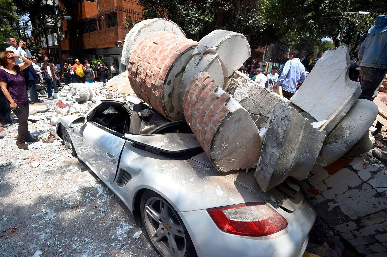 Un automóvil aplastado por los escombros de un edificio dañado en la Ciudad de México.