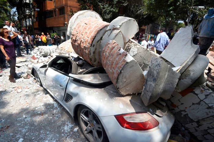 A car smashed by debris from a damaged building in Mexico City.