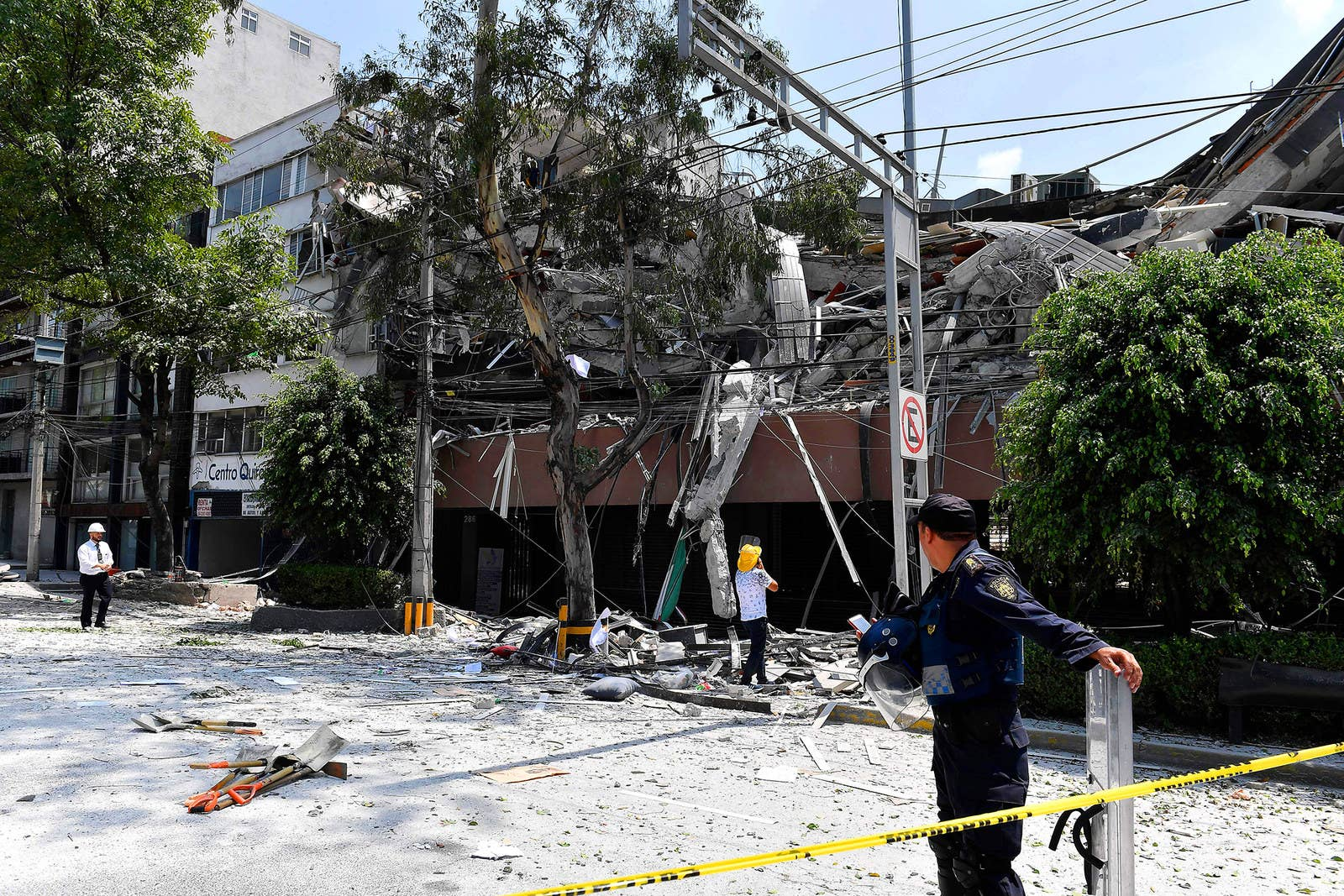 Un oficial de policía y otras personas inspeccionan un edificio que colapsó.