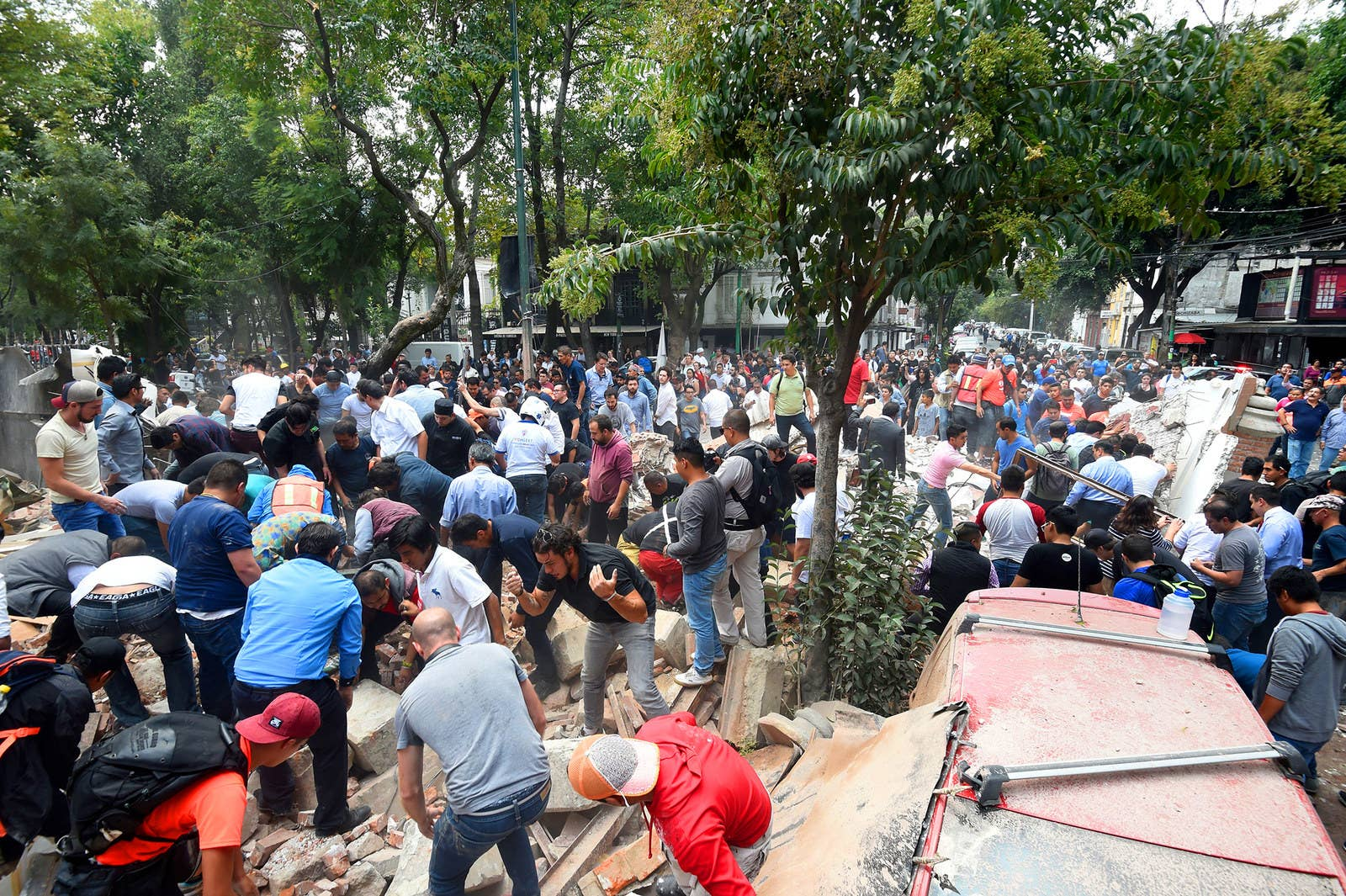 Personas remueven los escombros de un edificio en la ciudad de México.