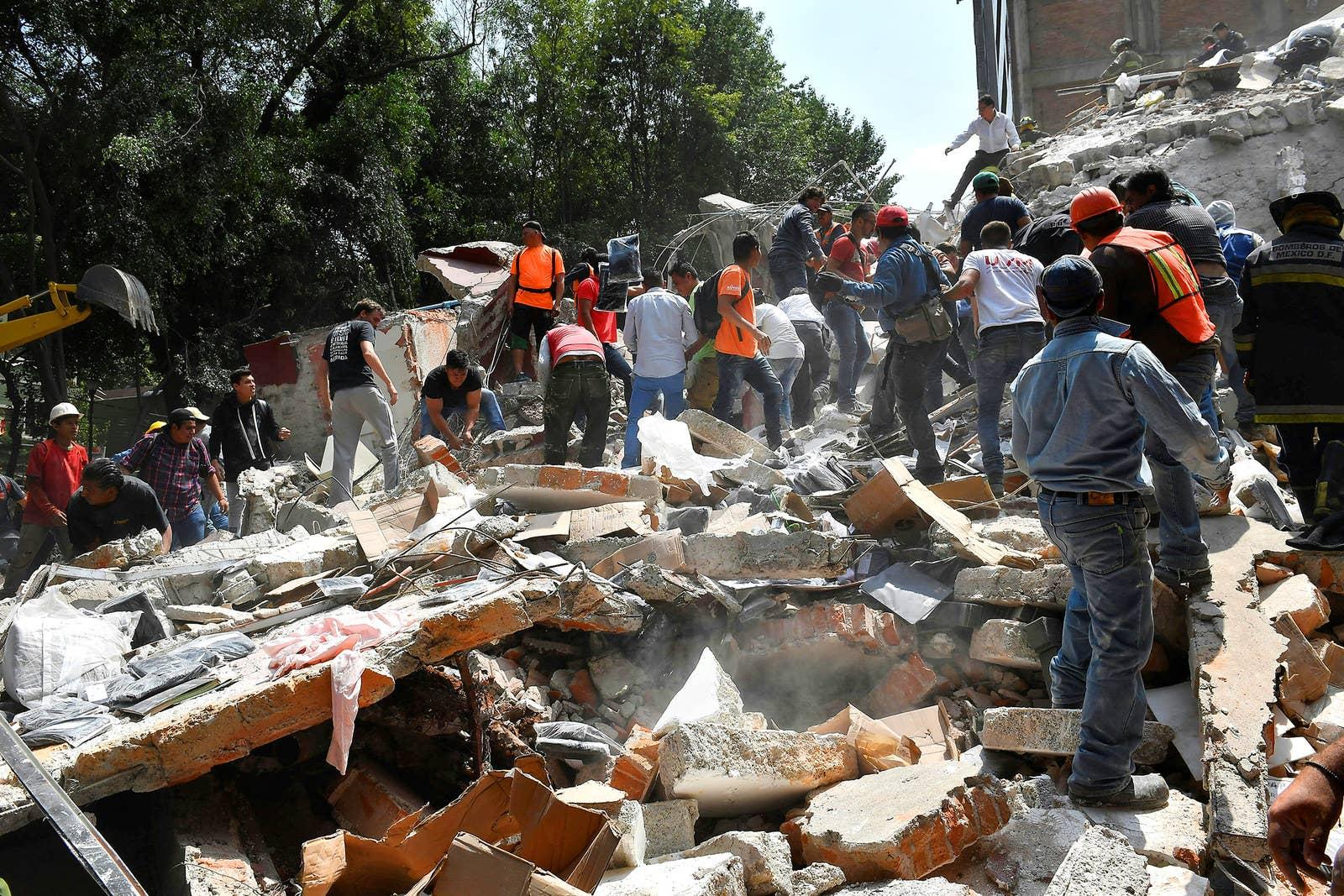 Personas remueven los escombros de un edificio que colapsó durante el terremoto.