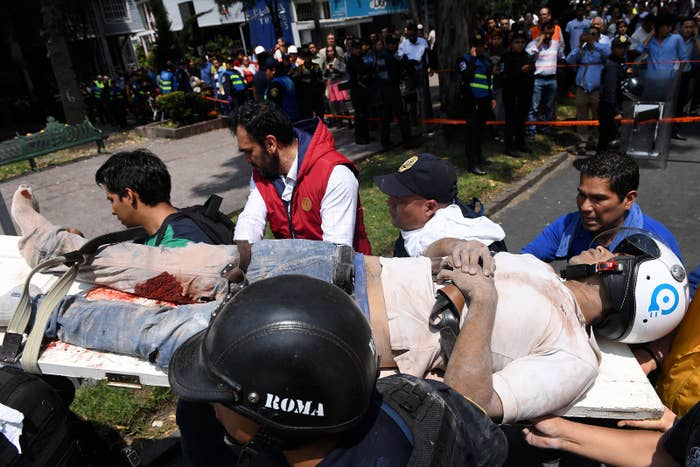 A man is carried on a stretcher after being pulled out of the rubble in Mexico City.
