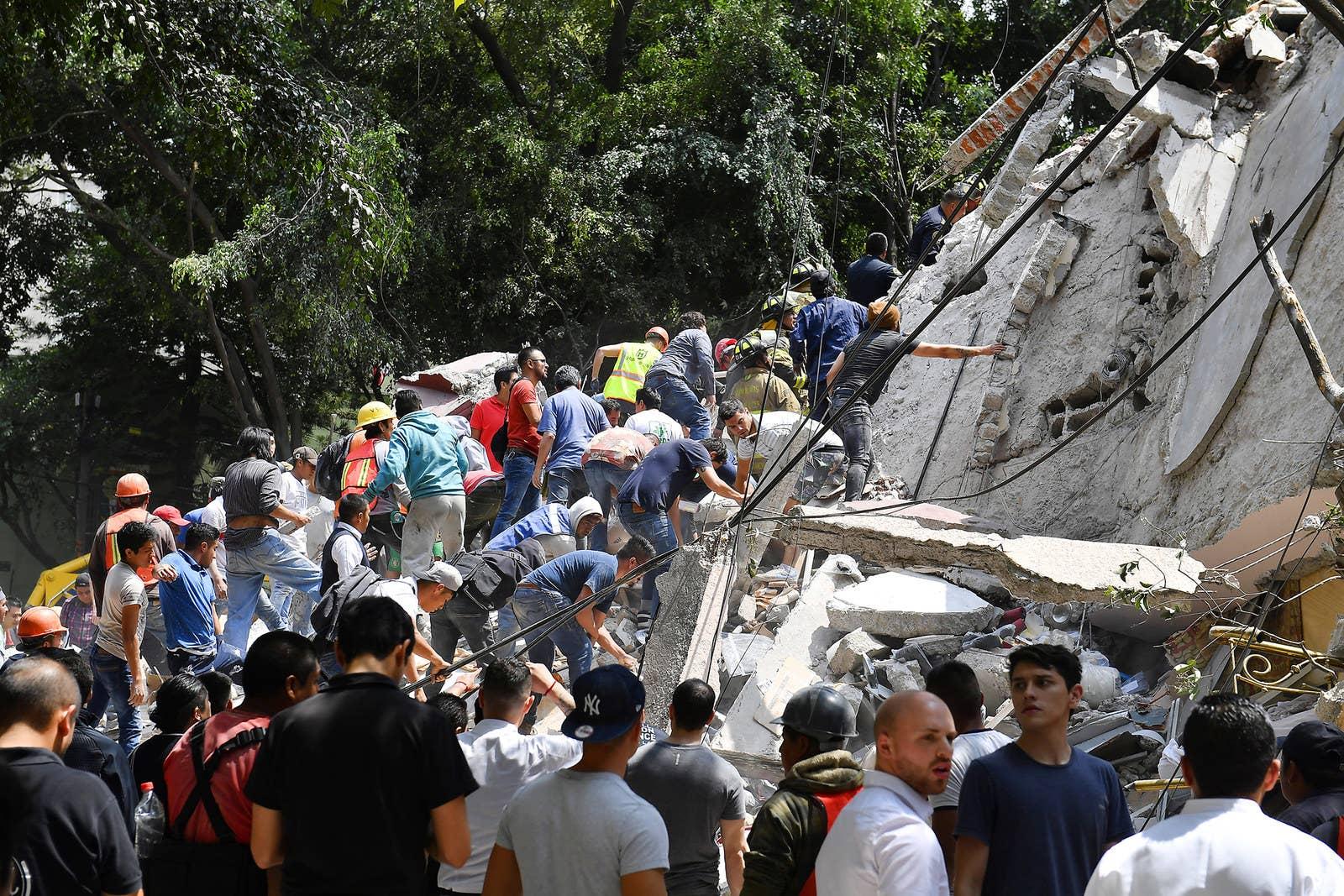 Personas remueven los escombros de un edificio colapsado en busca de posibles víctimas.