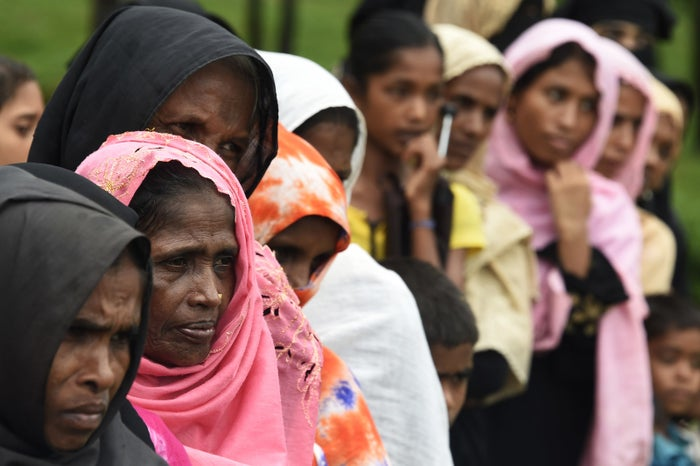 Rohingya refugees wait in line for relief supplies in a refugee camp.