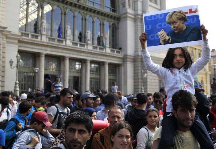 A young girl holds up a picture of Merkel as migrants set off on foot for the border with Austria from outside Keleti station in Budapest, 4 September 2015.