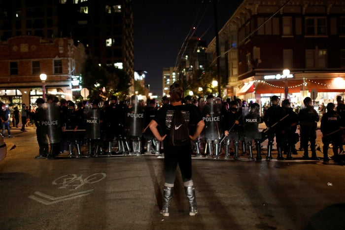 A protester faces off with police in the Central West End neighborhood of St. Louis Friday.