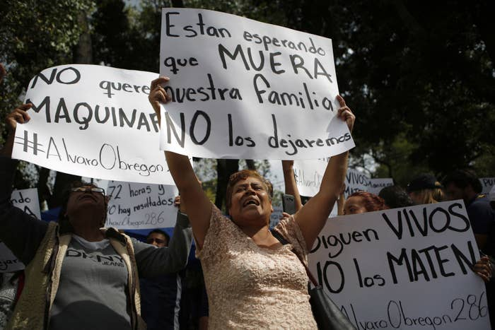 """Family members holding signs that read in Spanish """"They are waiting for our family to die,"""" """"They are still alive. Don't kill them."""""""