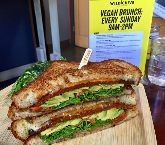 """Down in Long Beach there's a pop-up restaurant named The Wild Chive that serves a damn fine vegan grilled cheese sandwich. The Wild Chive is first on this list because it's the first place we stopped at, but - spoiler alert - it was also the best grilled cheese sandwich we had during our vegan grilled cheese tour. The toast is incredibly buttery, the two types of cheese very gooey, the aioli spread tangy, and it's packed with hickory """"bacon"""", arugula, and a generous amount of avocado. This is a really fantastic sandwich. It even comes with a side salad.Wild Chive is pop-up restaurant in Long Beach that can be found every Sunday at Portfolio Coffeehouse at 2300 E 4th St, Long Beach, CA 90814."""