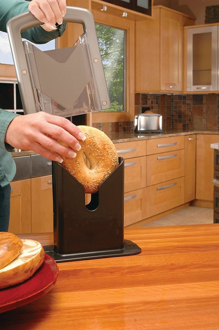 """Promising Review: """"How did I ever get by without this? For years, I sliced bagels with a knife. Now my bagels always slice evenly, and I don't have a crumby mess on the counter. So easy to use. So easy to clean. The blade cuts easily, but, it's safely away from my fingers."""" —TAMMY L NORRBOMPrice: $16.85+ Rating: 4.7 out of 5 Colors: three"""