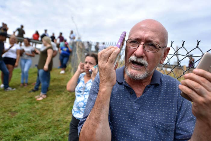 A man manages to speak by cellphone to his family from Vega Alta, Puerto Rico, on Sept. 23.