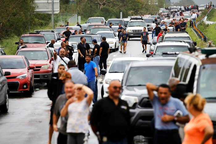People are pictured stuck in a jam on a expressway blocked by a flooded river in Yauco, Puerto Rico, on Sept. 21.