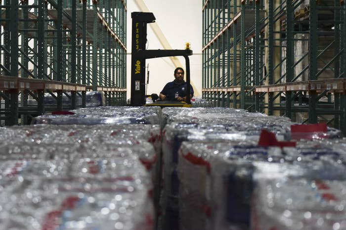 A worker moves bundles of water bottles at a FEMA Central Warehouse in San Juan, Puerto Rico, Tuesday.