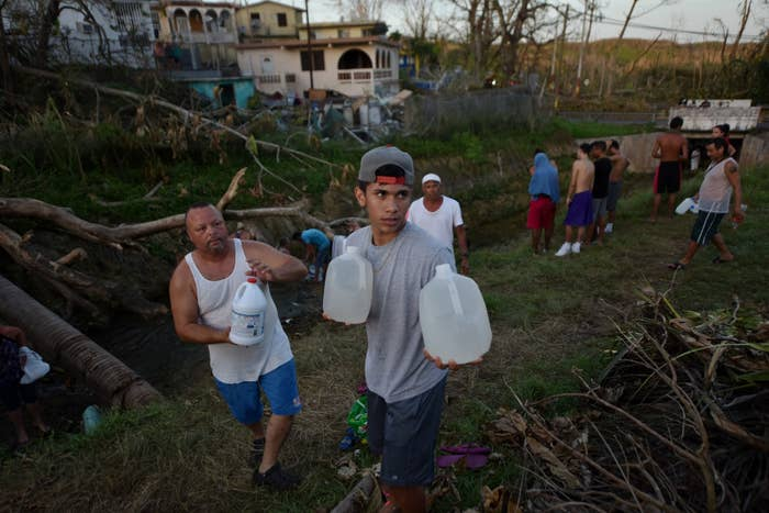 People carry water in bottles retrieved from a canal in Toa Alta, Puerto Rico, on Monday.