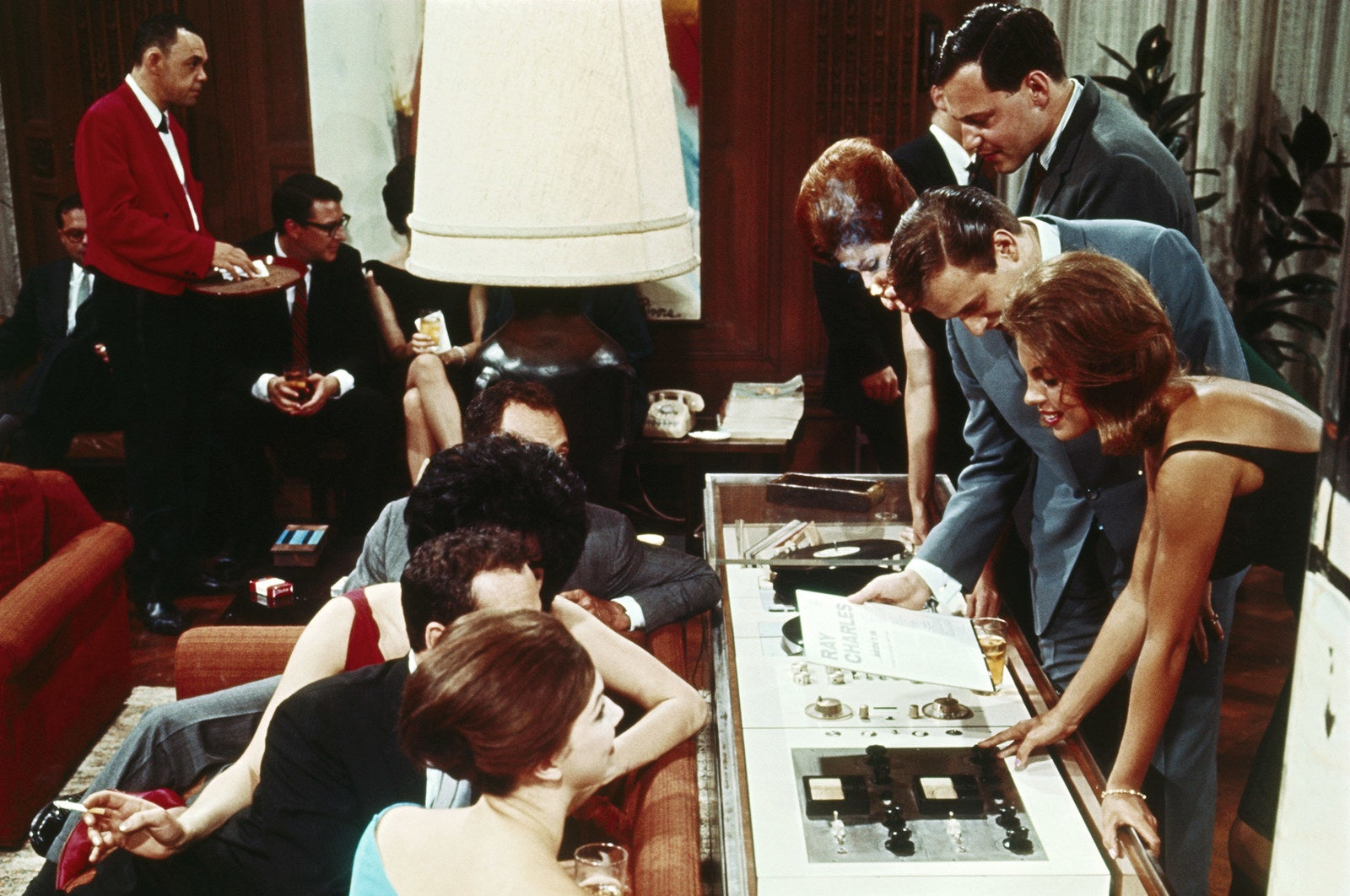 A crowd of partygoers inspect Hefner's stereo system at his Playboy Mansion in Chicago, circa 1966.