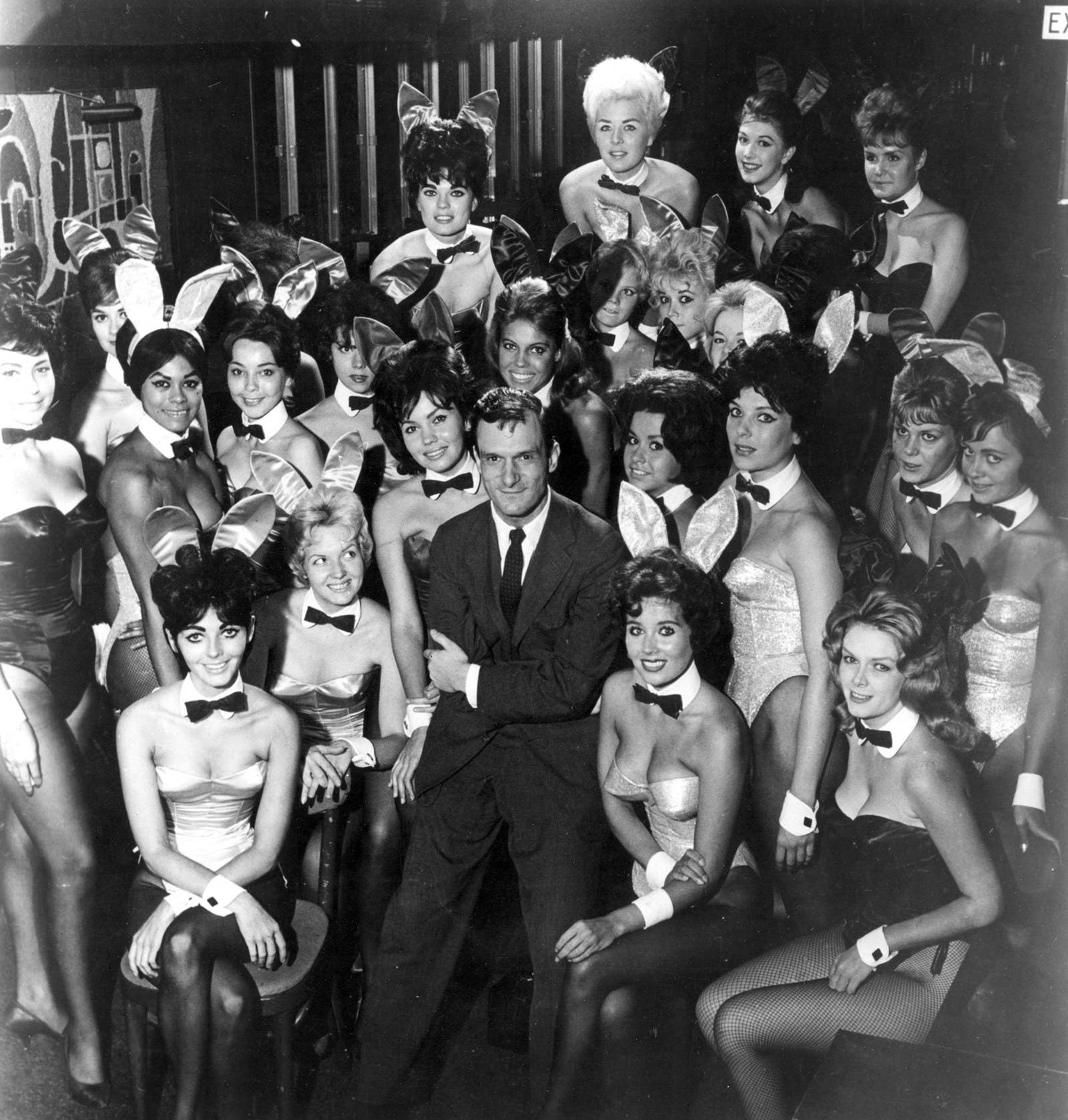 Millionaire publisher of Playboy magazine Hugh Hefner poses with Playmate Bunnies at one of his clubs in 1962.