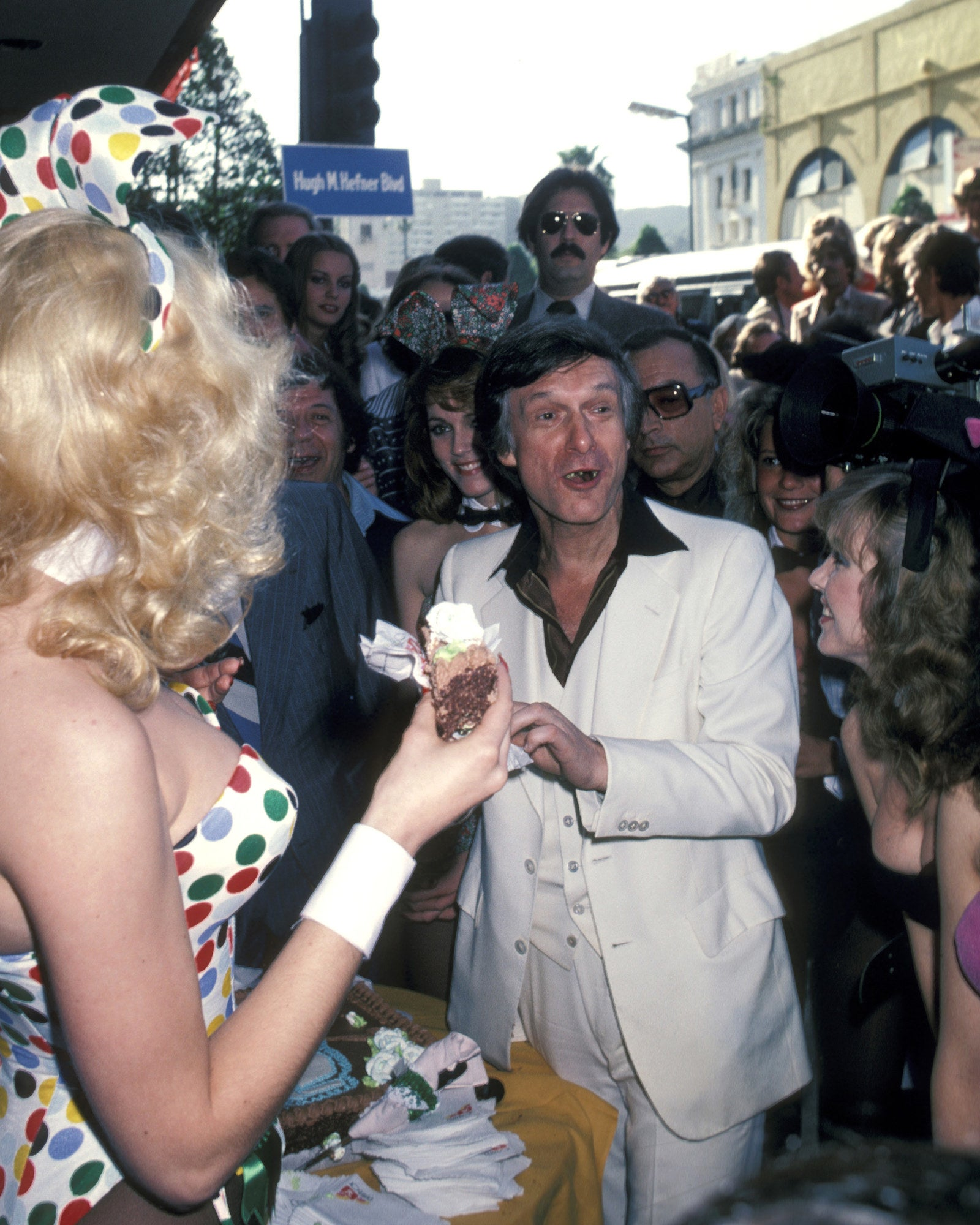 Hefner and Playboy Bunnies celebrate as he receives a star on the Hollywood Walk of Fame in 1980 for his achievements in television.