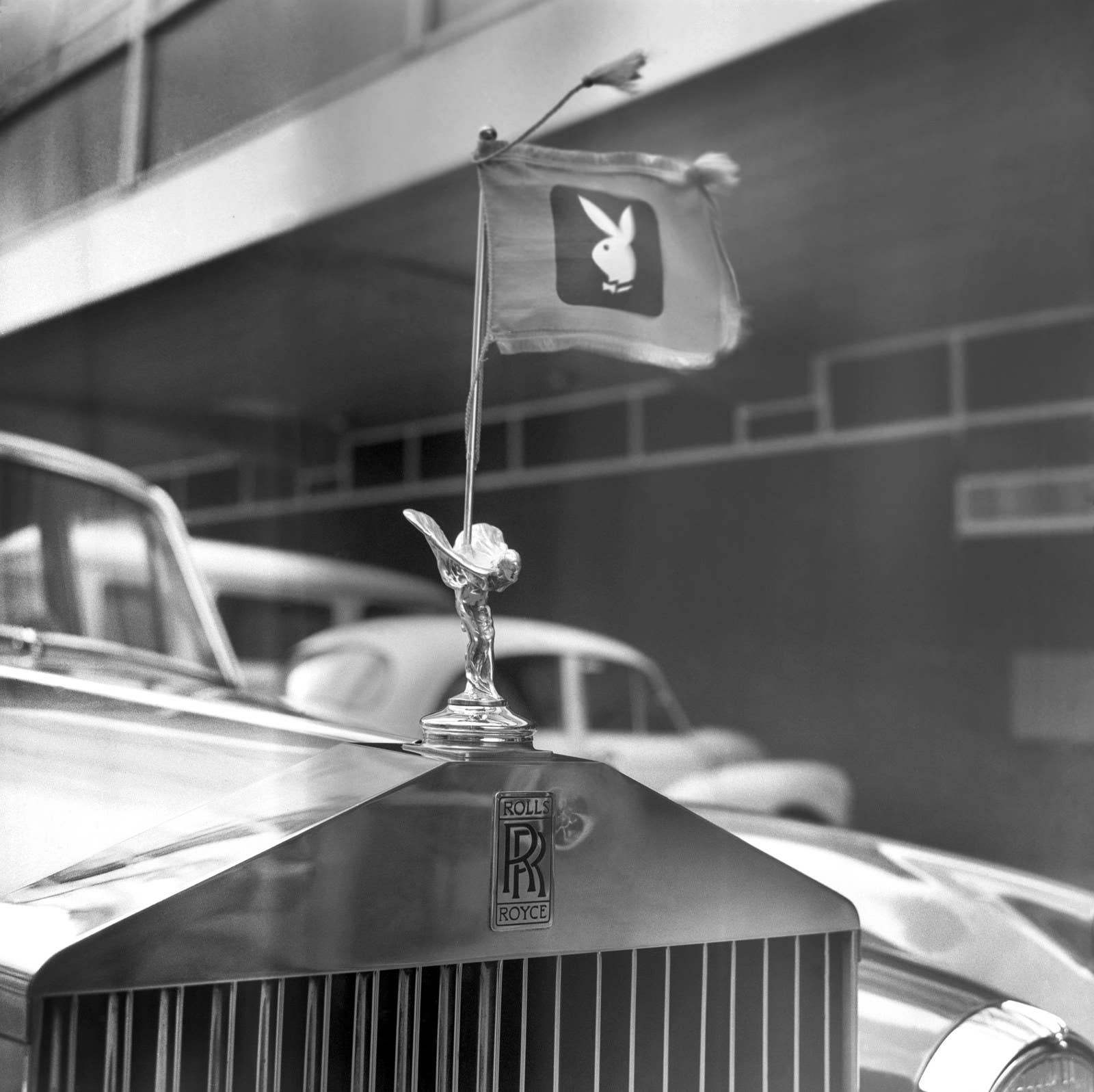 "The ""badge of the bunnies"" on a Rolls-Royce picks up Hefner after arriving from the US in 1966."