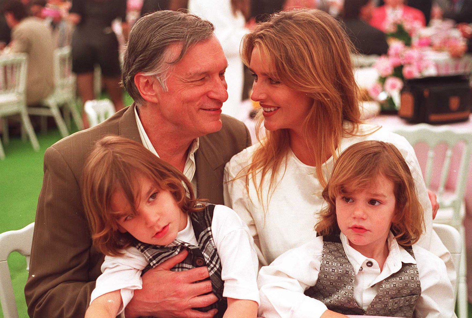 Hefner sits with his wife Kimberley and two children during an event at the Playboy Mansion in April 1994.