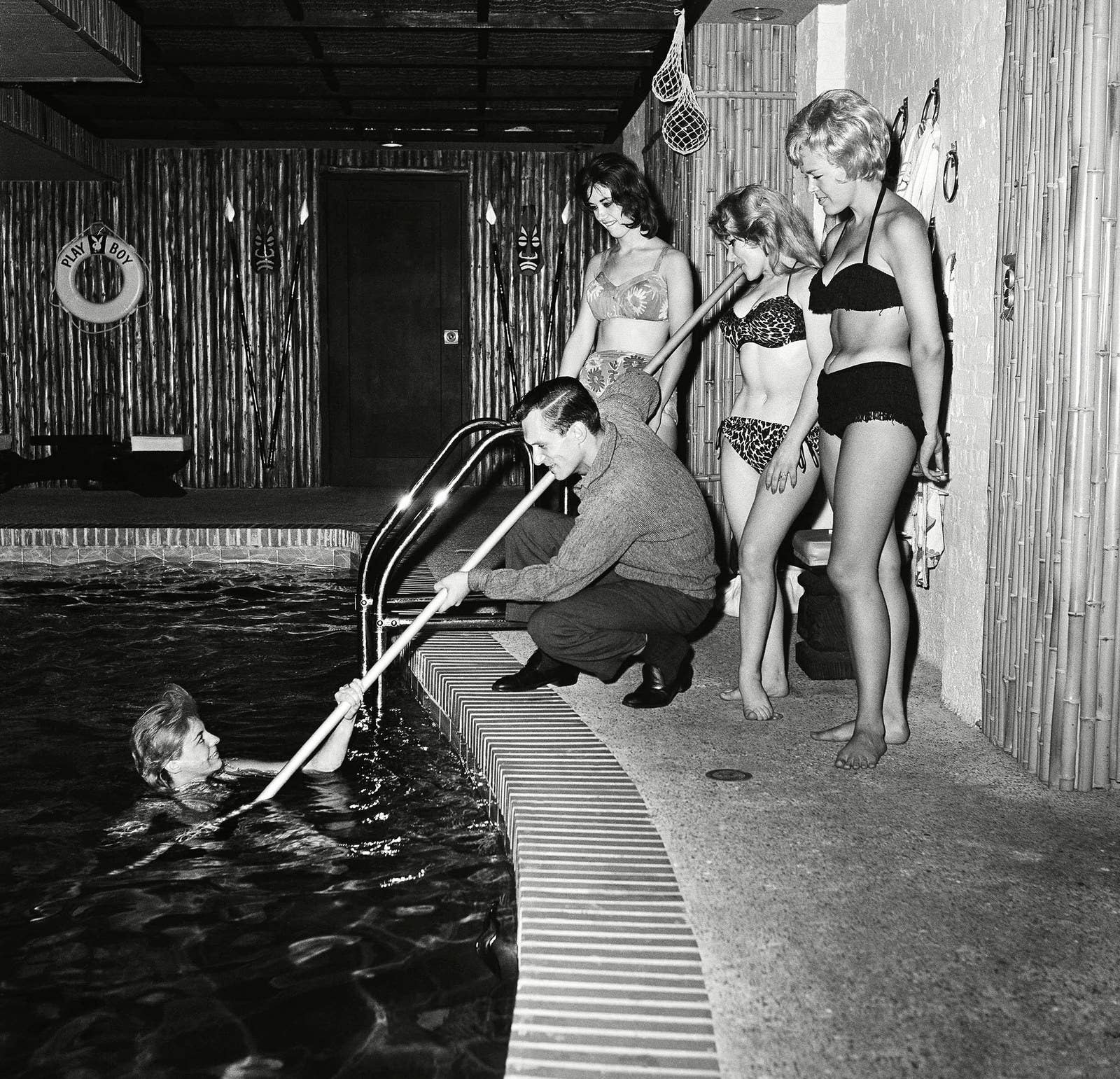 "Hugh Hefner ""rescues"" one of the swimmers in the indoor pool of his Chicago apartment in 1961."