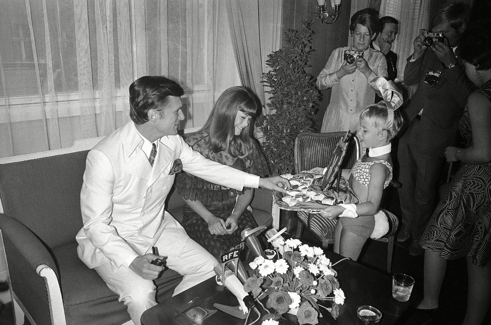"During a press conference, a little ""Bunny"" offers sweets to Hugh Hefner and his girlfriend Barbara Benton after they arrived in West Berlin to shoot the film What Is A Nice Girl Like You Doing In This Business, in 1969."