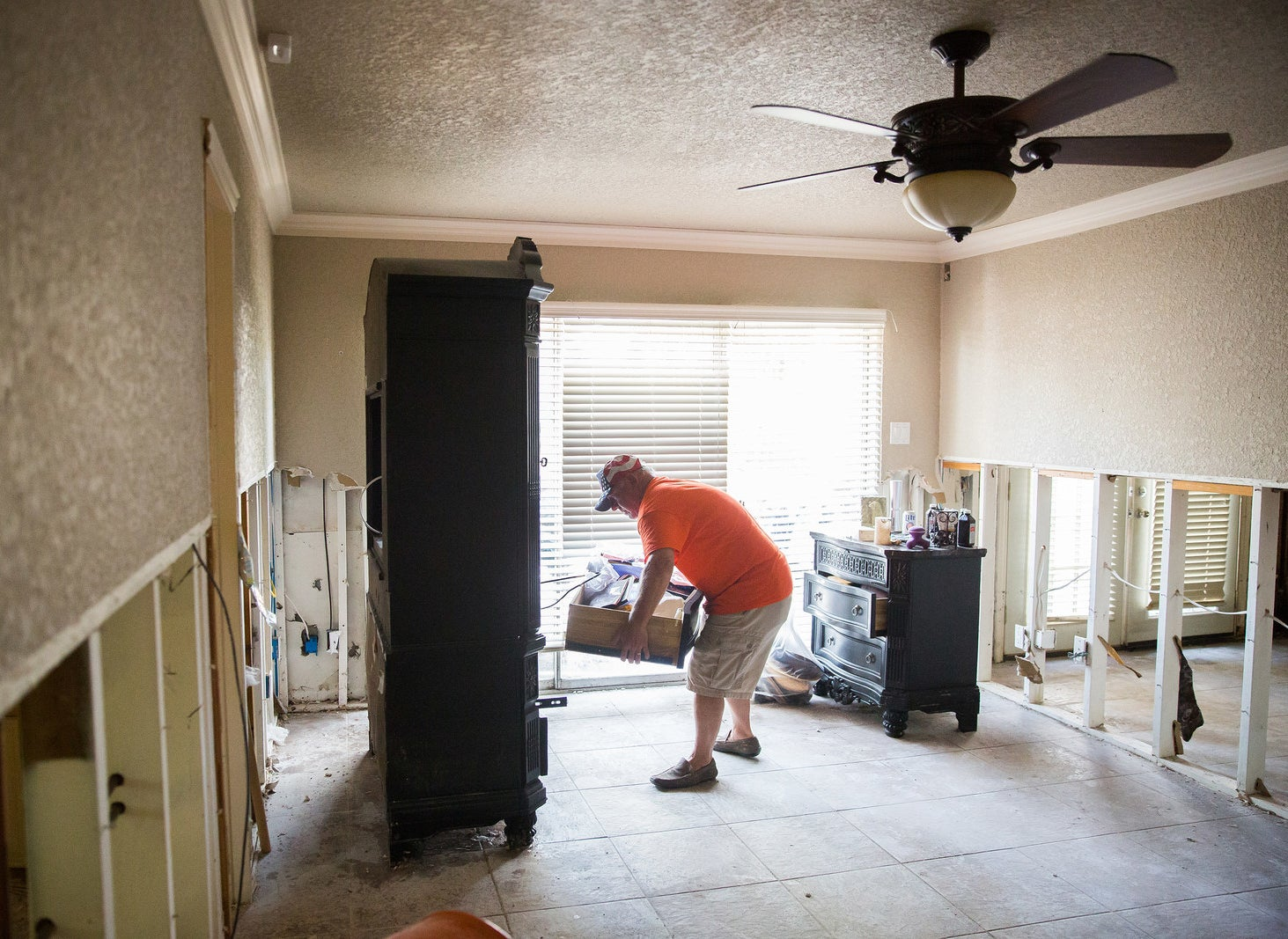 Dan Faust empties an armoire in his flood damaged bedroom.