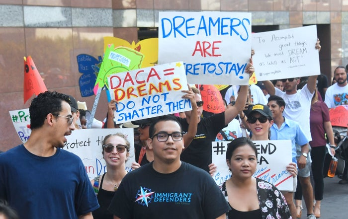 Young immigrants and supporters walk holding signs during a rally in support of Deferred Action for Childhood Arrivals in Los Angeles on Sept. 1.