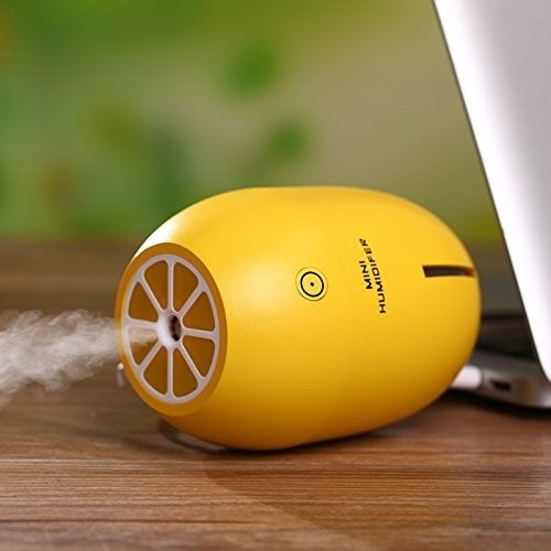 """It comes with a USB cord, so you can plug it into a car (it'll fit in the cup holder), laptop, or battery pack. It holds up to 180 milliliters of water, which is enough to run for approximately five to six hours. After four hours of running continuously, it automatically shuts off. Oh, and the top lights up!Promising review: """"Nice and portable humidifier! It's cute and small but can produce a good amount of mist. Great for office use and easy to carry when traveling."""" —Amazon CustomerGet it from Amazon for $11.99 (available in green and yellow)."""