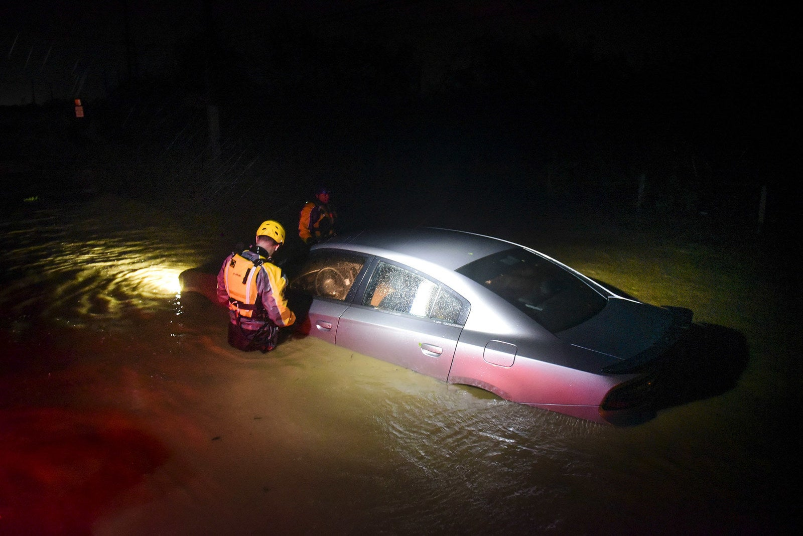 Rescue staff from the Municipal Emergency Management Agency investigate an empty flooded car during the passage of Hurricane Irma through the northeastern part of the island in Fajardo, Puerto Rico.