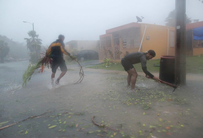 People pick up debris as Hurricane Irma howls past in Fajardo, Puerto Rico, on Wednesday.