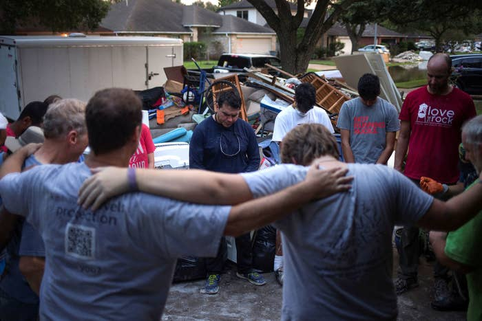 A group of people lock arms in prayer after helping clear furniture from the flooded house of a neighbor in the aftermath of Harvey in Houston on Sept. 3.