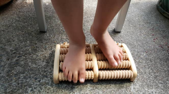 Reviewer using the abacus-like foot roller on their feet