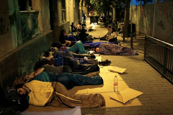 Padres y ciudadanos acampan en la entrada del colegio Reina Violant, uno de los colegios electorales designados en Barcelona.