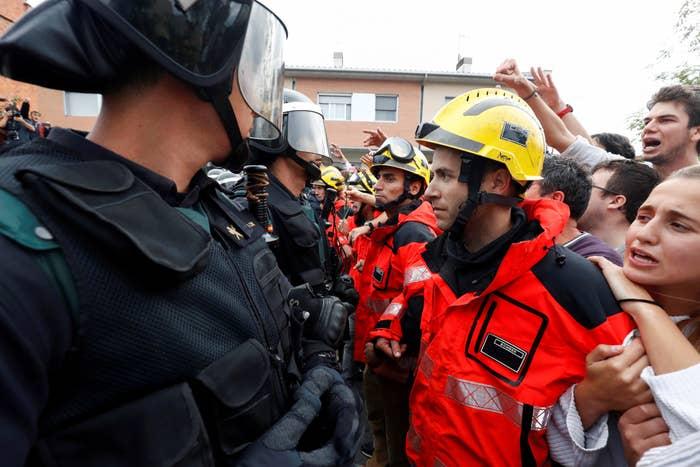 Los bomberos se interponen entre la policía y los protestantes a la salida de un colegio electoral en Barcelona.