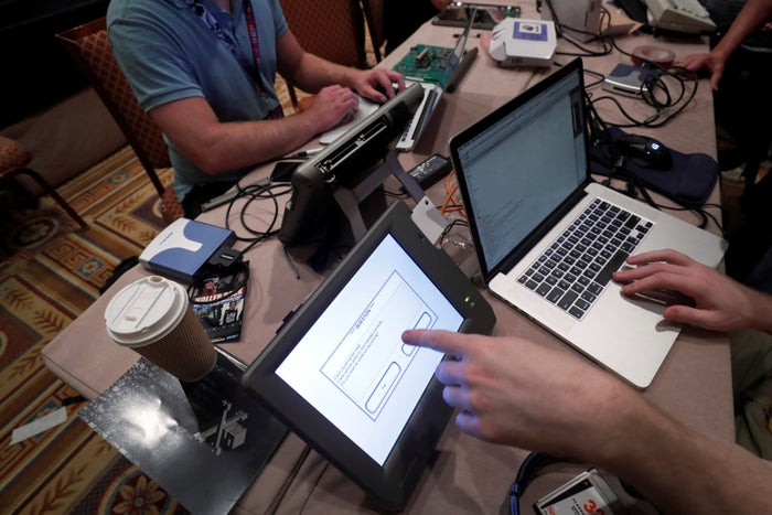 Hackers try to access and alter data from electronic poll books in the Voting Village during the DEF CON hacker convention in Las Vegas.