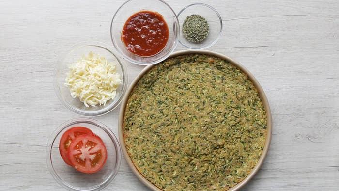 1. Preaqueça o forno à 220°C.2. Em uma tigela coberta com um pano de prato limpo rale as abobrinhas com um ralador usando a parte grossa.3. Salpique 1 colher de chá de sal e misture bem. Reserve por 20 minutos até que as abobrinhas soltem água e murchem. Esprema bem o pano para retirar todo o excesso de água.5. Coloque a abobrinha em uma uma tigela com ovos, queijo, farinha de trigo e farinha de rosca. Tempere com sal e pimenta, misture bem.6. Transfira para uma assadeira redonda untada (30cm), pressione bem e alise uniformemente.7. Leve ao forno 220°C por 20 minutos ou até ficar levemente dourado. Retire do forno.8. Baixe a temperatura do forno para 200°C.9. Espalhe sobre a base assada molho de tomate, queijo muçarela ralado, tomate e orégano.10. Leve ao forno por 15-20 minutos ou até que o queijo derreta.11. Aproveite!