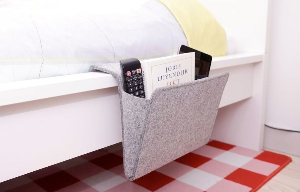 the bedside caddy with a remote and other items inside