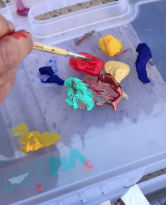 The camera quickly zooms into some paints and then...