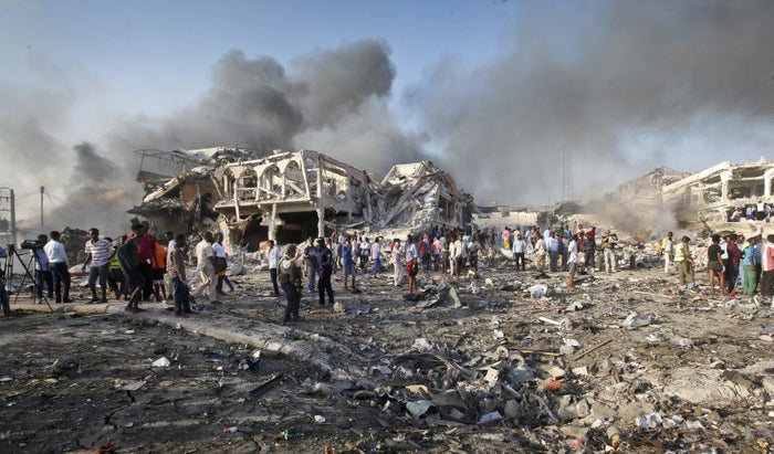 Somalis gather and search for survivors at the scene of a blast.