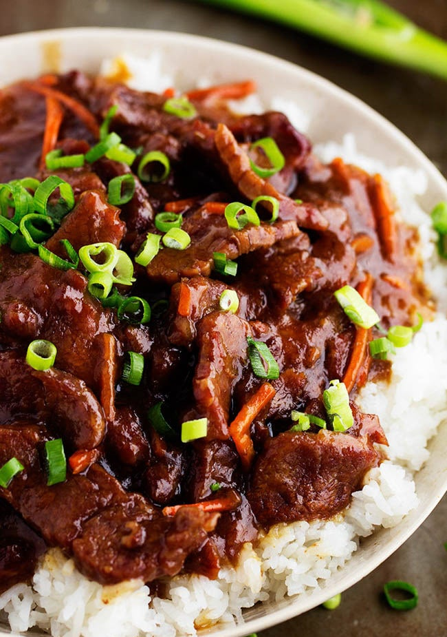 A bowl of white rice topped with sticky Mongolian beef and scallions.
