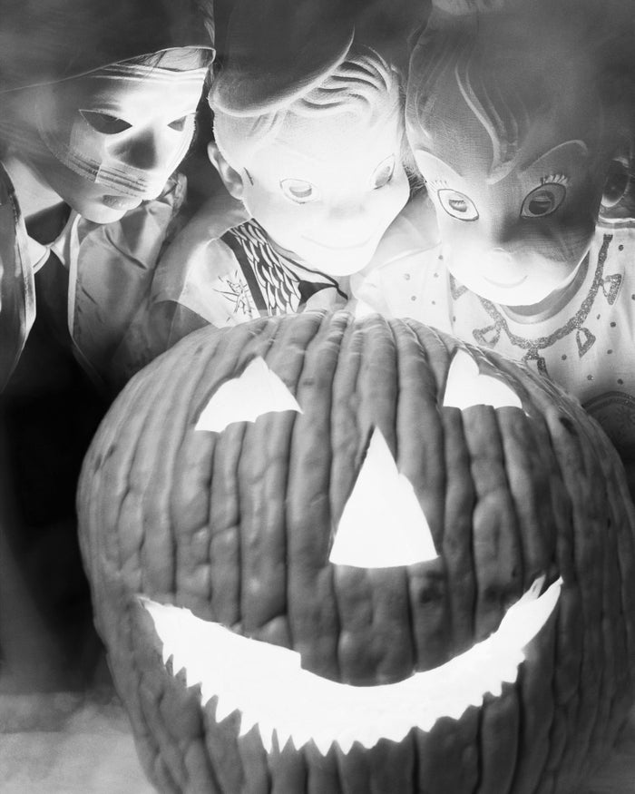 Three masked five-year-olds with a jack-o-lantern in Chicago, 1954.