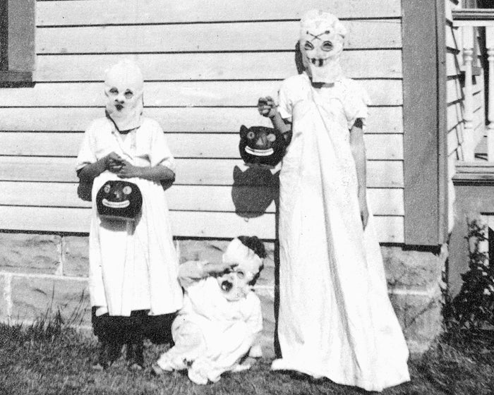 Three kids dressed as ghosts are ready for trick-or-treating, circa 1925.