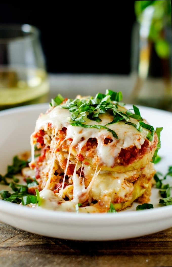 A slice of cheesy, breaded eggplant parmesan with fresh basil.