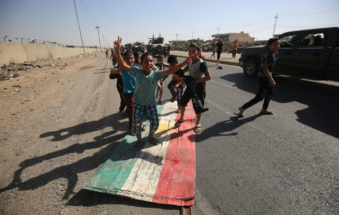 Iraqi children step on a Kurdish flag as forces loyal to the central government in Baghdad advance toward the center of Kirkuk on Monday.