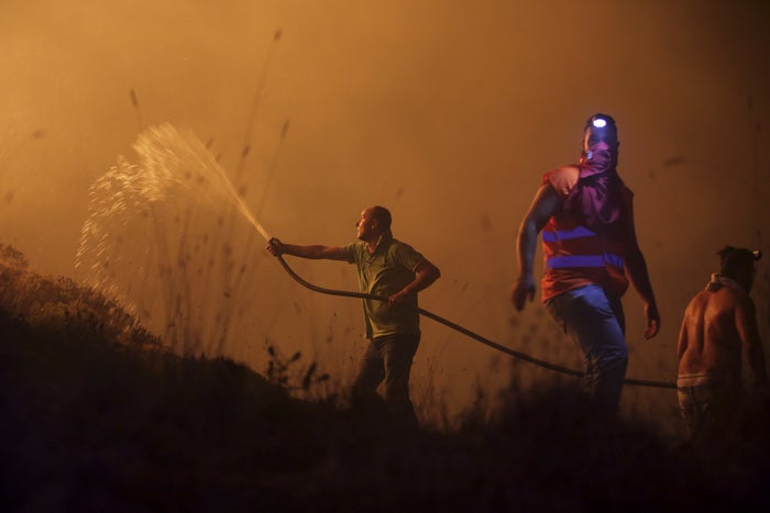 Volunteers use a water hose to fight a wild fire raging near houses in the outskirts of Obidos, Portugal.
