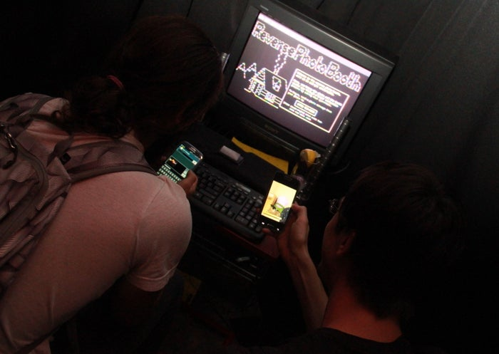 Two visitors to the Reverse Photo Booth browse their phones for a photo to send.