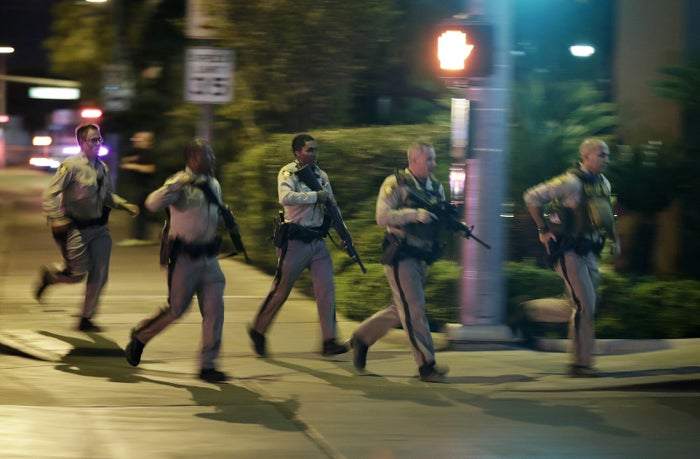 Police run for cover at the scene of a shooting near the Mandalay Bay in Las Vegas Sunday night.