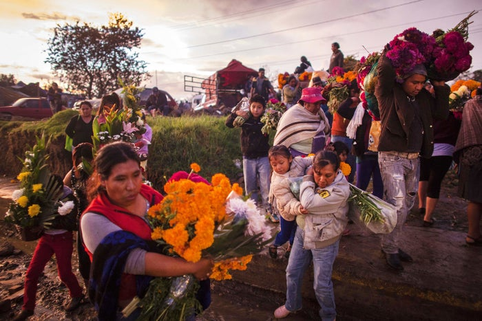 People carrying Mexican marigolds arrive at the local cemetery on Nov. 1, 2013, in San Miguel Canoa, Mexico.